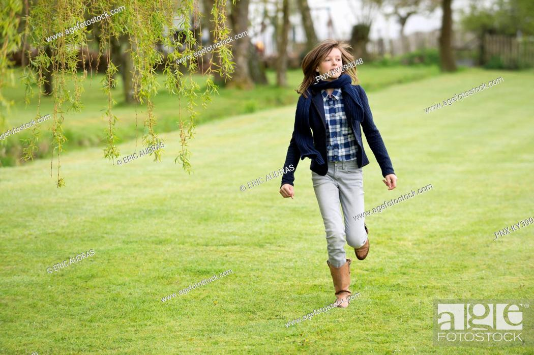 Stock Photo: Girl running in a field.