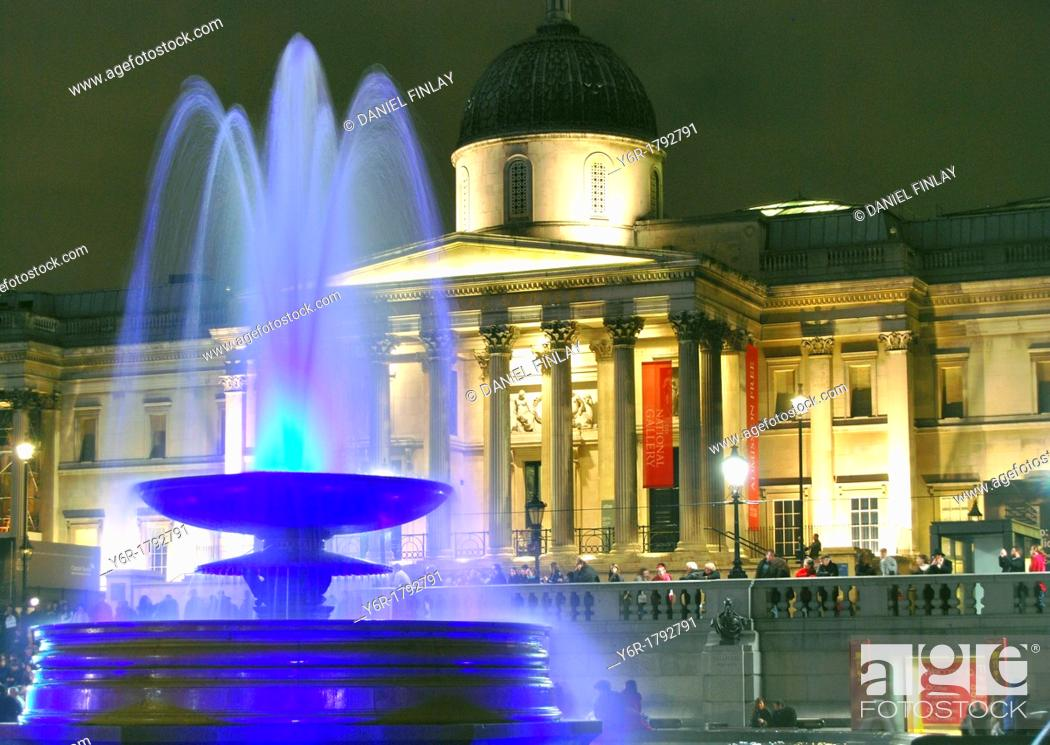 Stock Photo: Fountain in Trafalgar Square, London, England, lit up colourfully at night, with the National Gallery illuminated in the background.