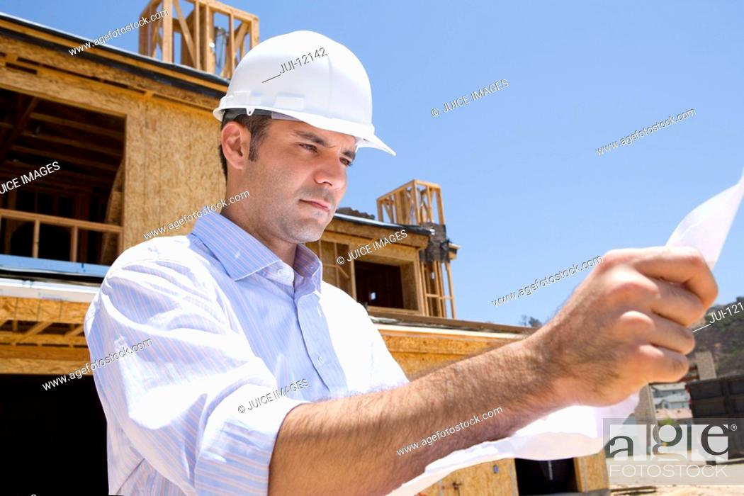 Stock Photo: Architect with blueprint in front of partially built house, low angle view.