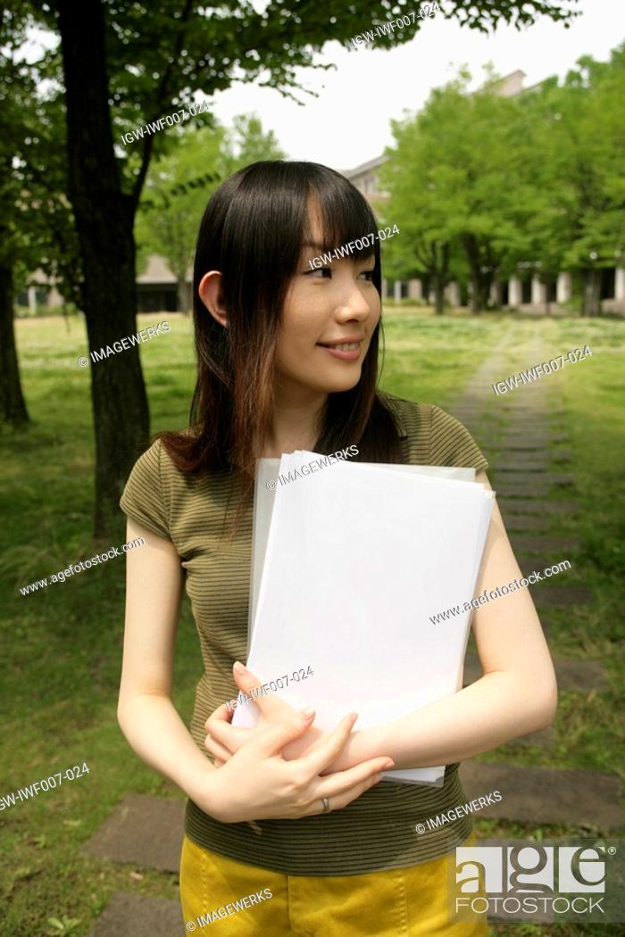 Stock Photo: A young woman holds files and papers while she stands amidst grass and trees.