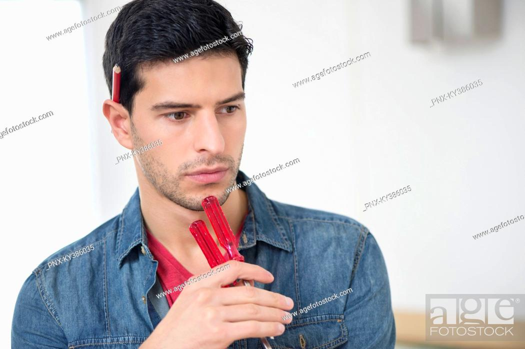 Stock Photo: Technician holding screwdrivers and thinking.