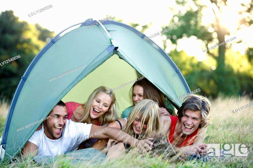 Stock Photo: A group of young people in a tent, laughing.
