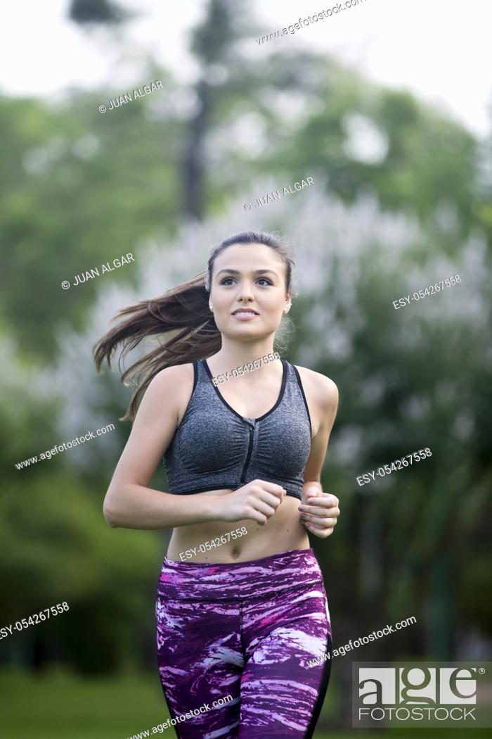 Stock Photo: Portrait of beautiful sportswoman smiling away while running in park. Bokeh.