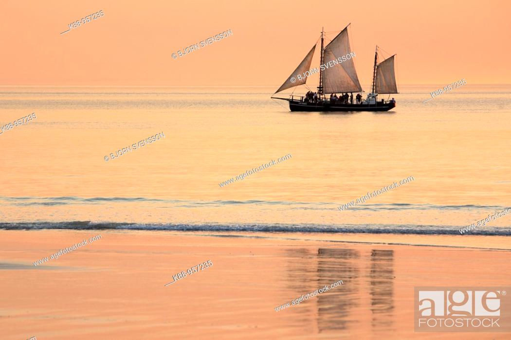 Stock Photo: Pearl lugger cruising past Cable beach at sunset. Broome, Western Australia.