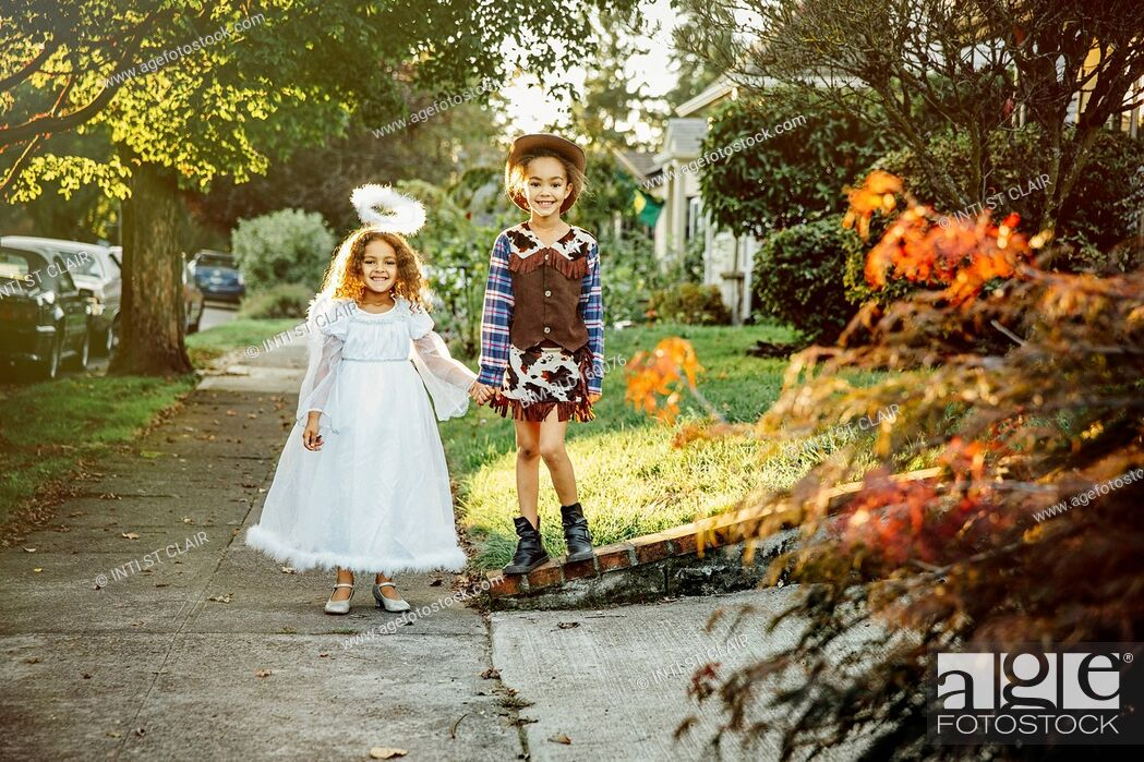 Stock Photo: Sisters wearing Halloween costumes on sidewalk.