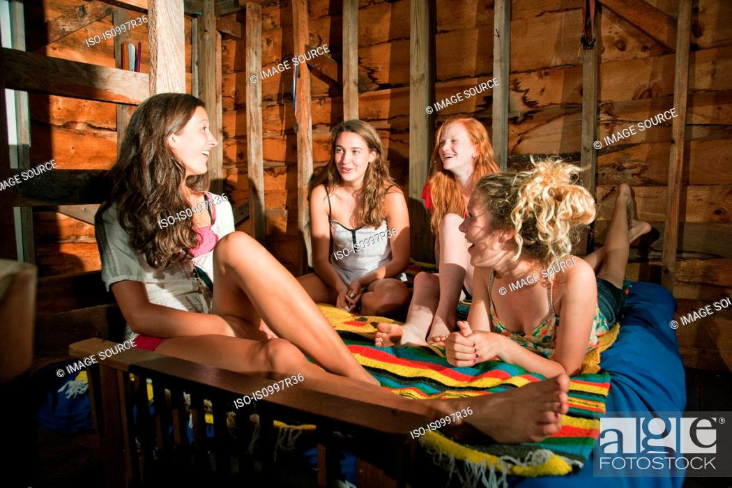 Stock Photo: Teenage girls chilling out together on bed in boat house.
