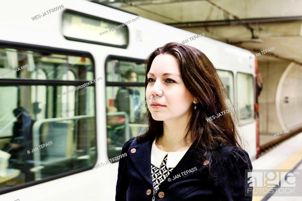 Imagen: Germany, Cologne, portrait of young woman waiting at underground station platform.