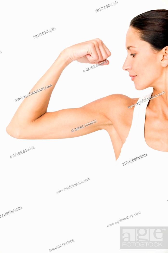 Stock Photo: Young woman flexing muscles.