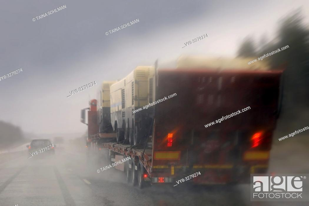 Stock Photo: Driving along highway in rain and passing a semi truck with a load of machinery, rainwater splashing, blurred view.