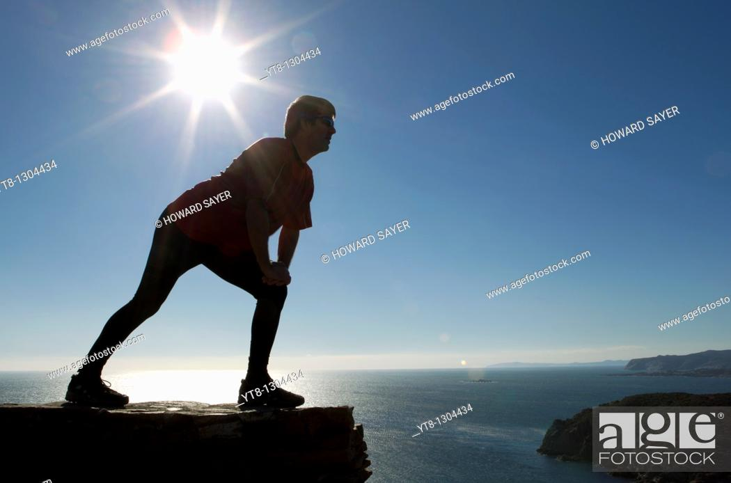 Stock Photo: Man performing stretching exercise by the sea.