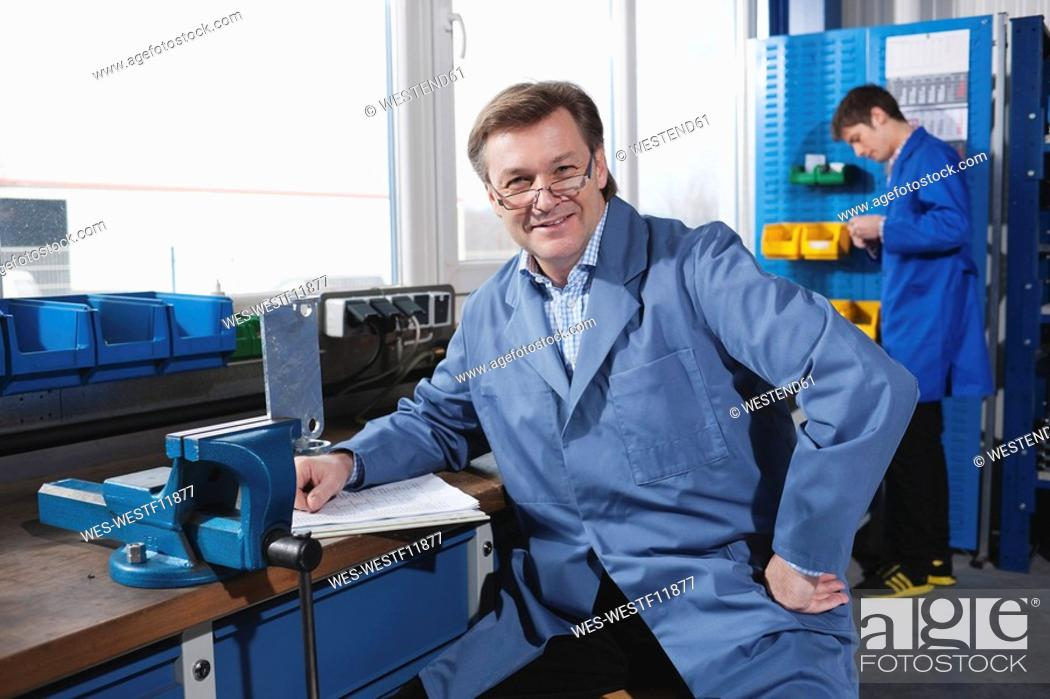 Stock Photo: Germany, Neukirch, Man sitting at work bench, Apprentice in background.