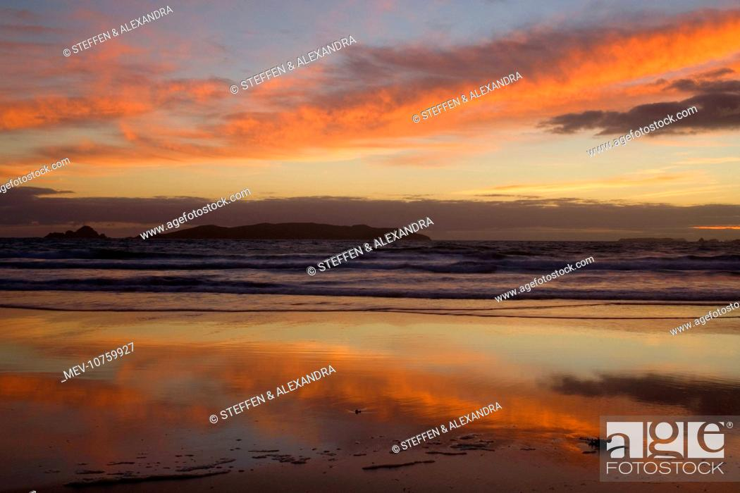 Stock Photo: Sunrise - spectacular sunrise over the ocean with clouds blazing in all hues of yellow and red and mirroring themselves on the wet beach.