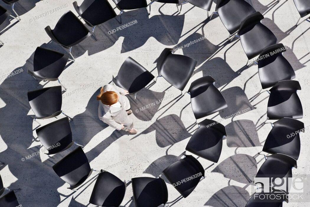 Stock Photo: Woman standing in spiral of office chairs.