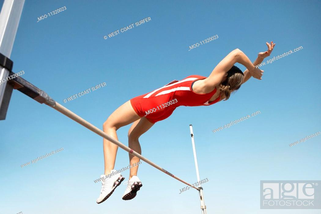 Stock Photo: High Jumper in mid air over bar view from below.