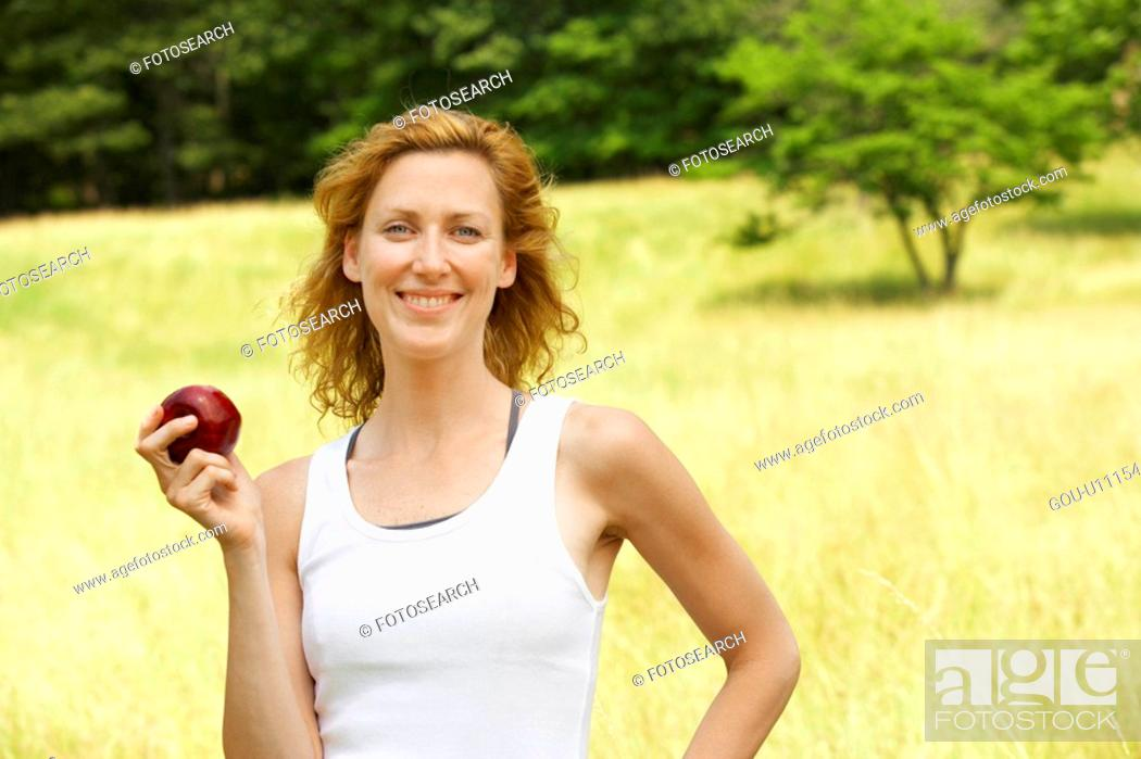 Stock Photo: Woman eating apple in field.