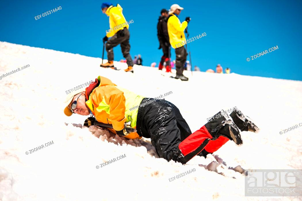 Photo de stock: Training to correct slip on a slope or a glacier with the help of an ice ax. A fully equipped backpacker slides on the belly along a snowy slope in the.