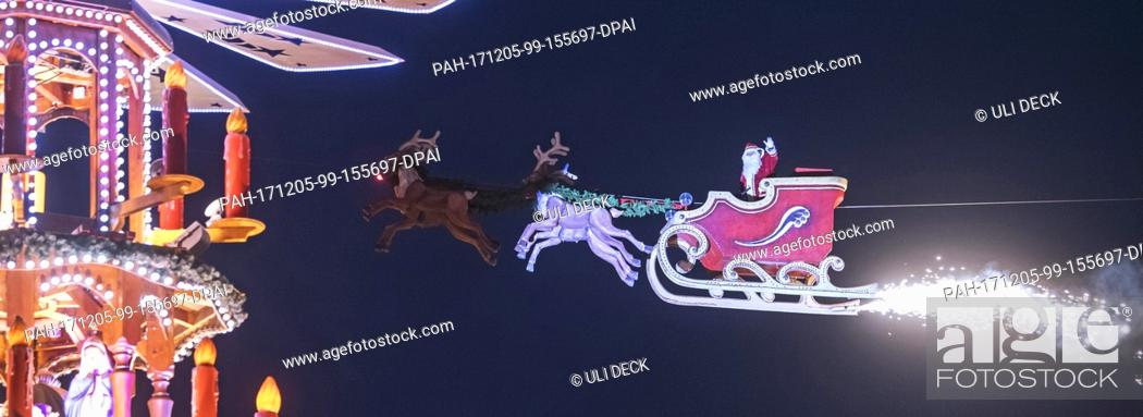 Stock Photo: The high-wire artist Falko Traber drives in a motor-powered sled dressed as Father Christmas over the Christmas market in Karlsruhe, Germany, 05 December 2017.