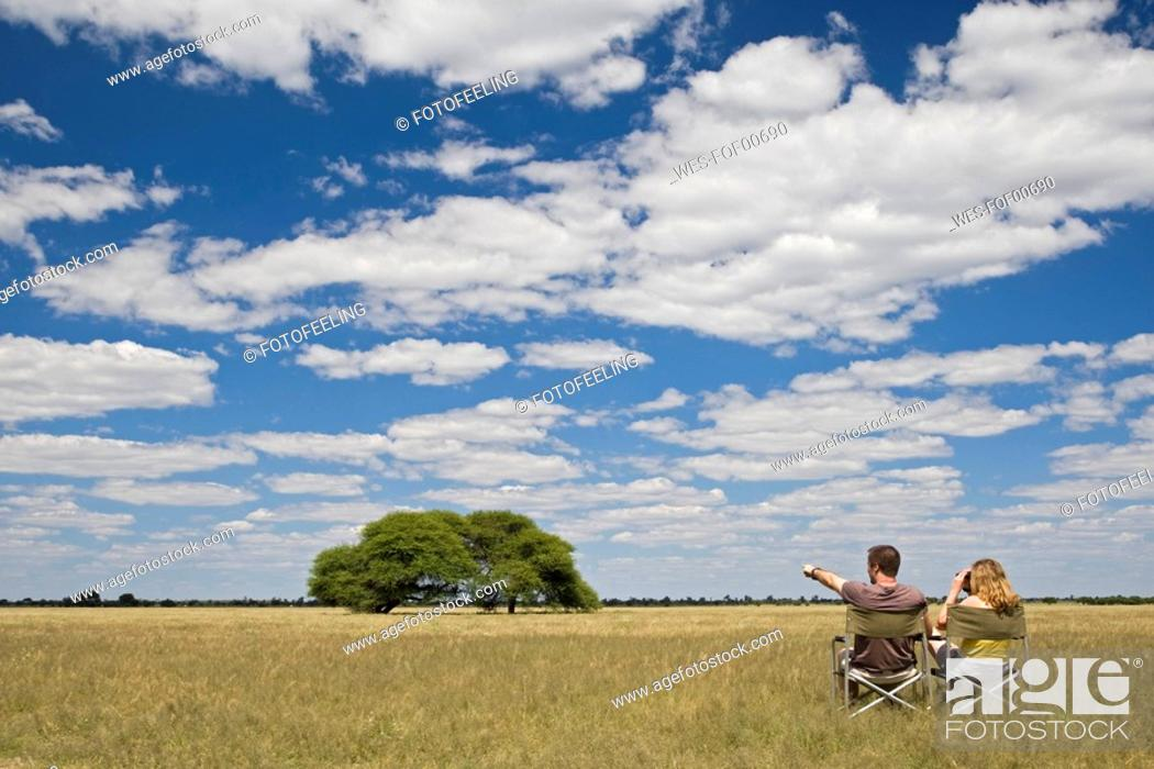 Stock Photo: Africa, Botswana, Tourists looking at the landscape.