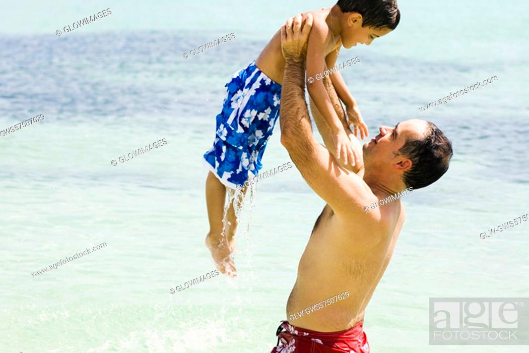 Stock Photo: Side profile of a mid adult man picking up his son in water.