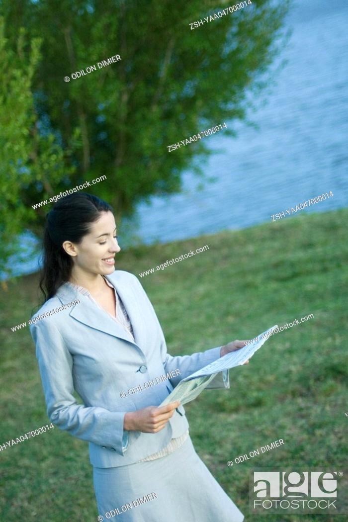 Stock Photo: Businesswoman reading newspaper in park.