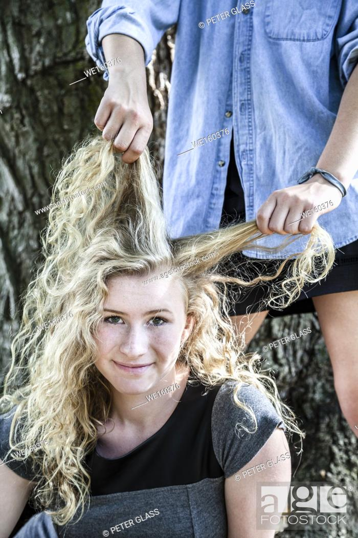 Stock Photo: Blonde teenage girl outdoors, with hands from another teenage girl pulling her hair.