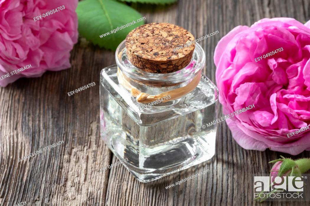 Stock Photo: A bottle of essential oil with fresh cabbage roses.