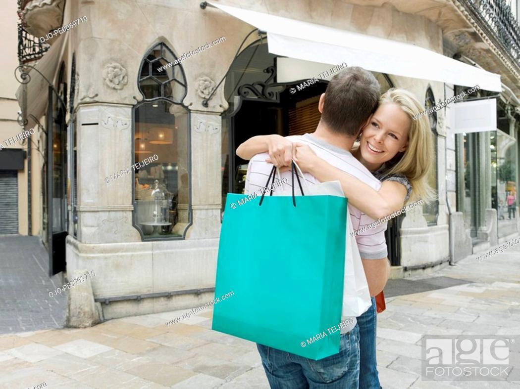 Stock Photo: Woman holding shopping bag hugging man.