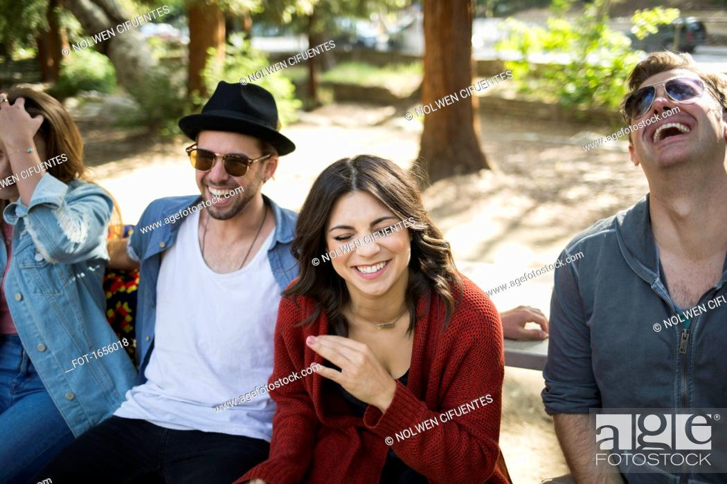 Stock Photo: Cheerful male and female friends sitting on bench at park.