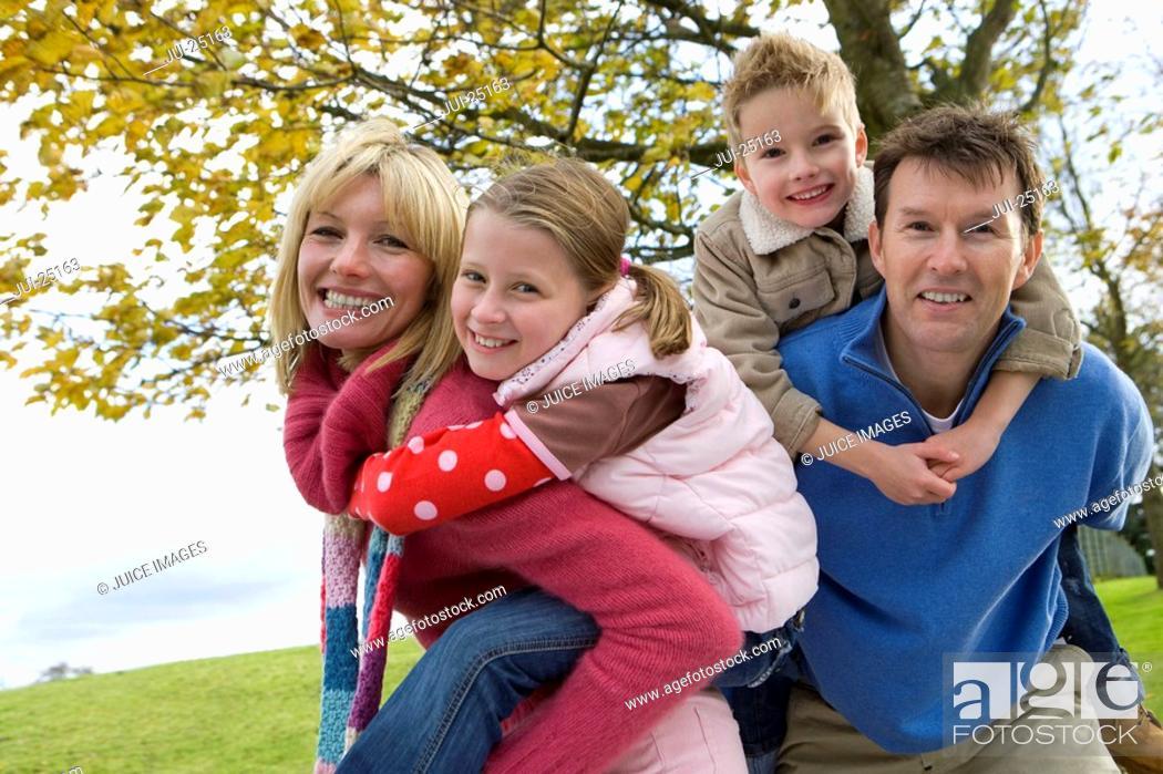 Parents giving children piggyback rides in park, Stock Photo