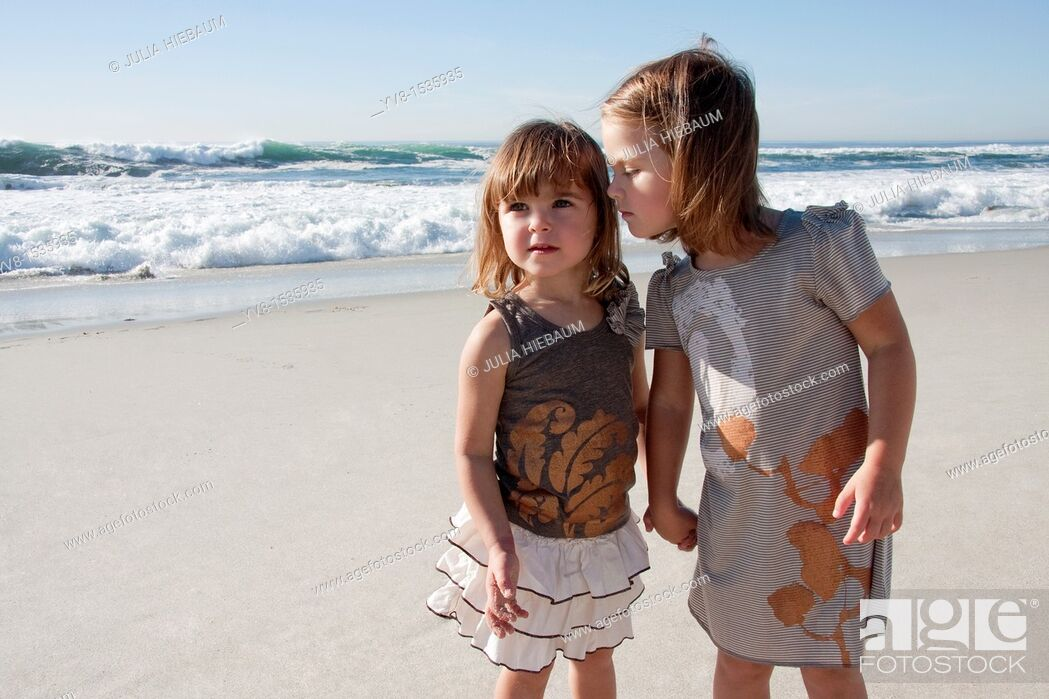 Stock Photo: Two baby girls holding hands at the beach.