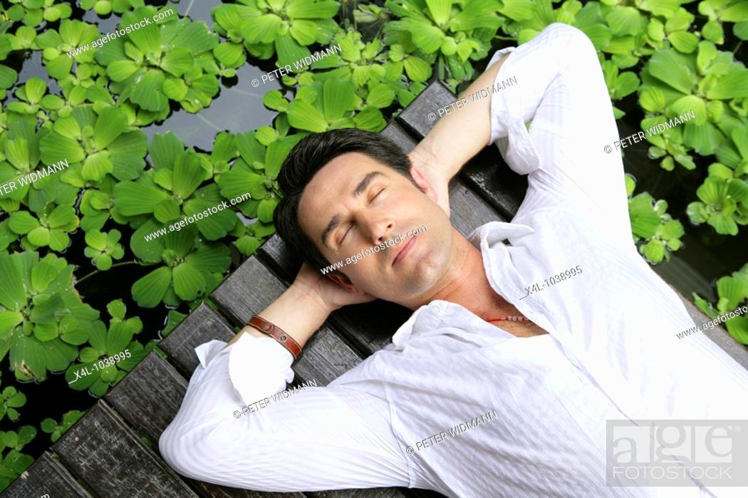 Stock Photo: Man enjoying holidays at tropical garden in Thailand.