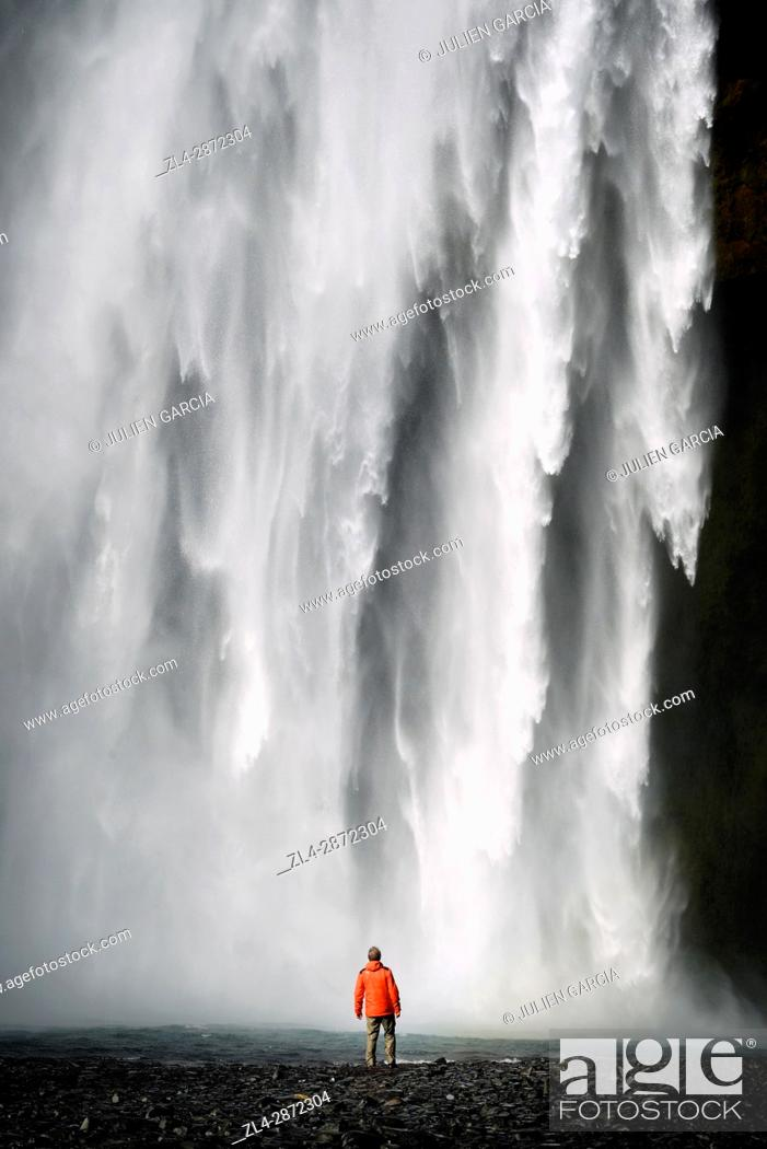 Stock Photo: Iceland, Sudurland region, man in front of Skogafoss waterfall.