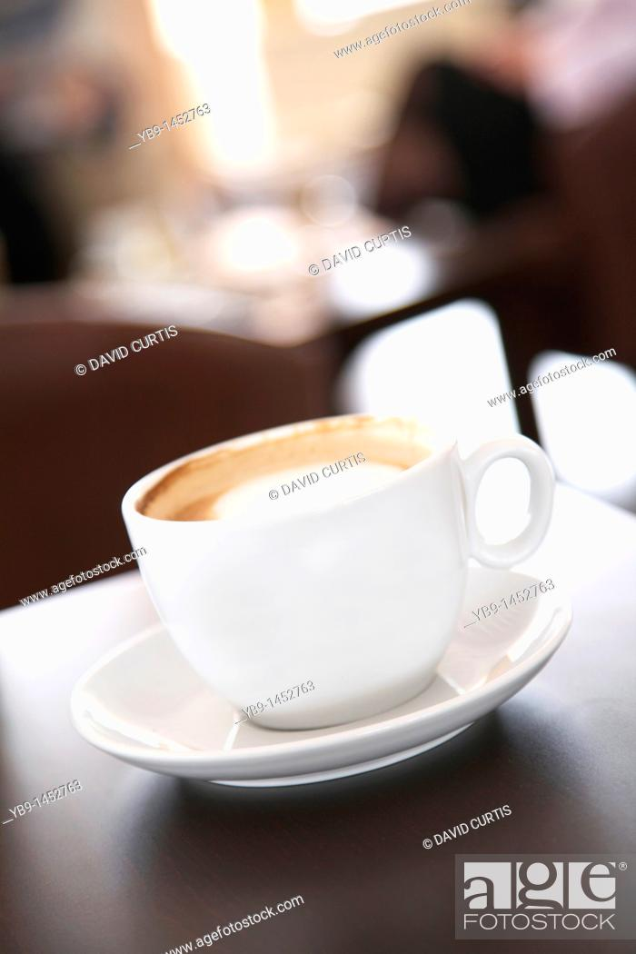 Stock Photo: Cup of cappuccino coffee on a table in a cafe.