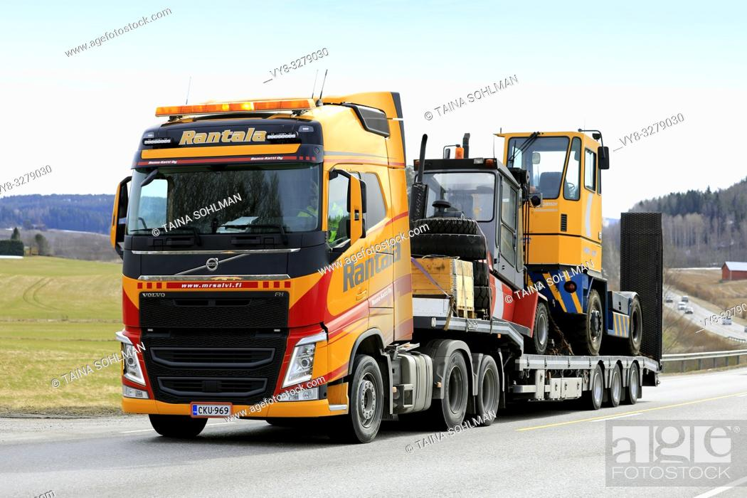 Stock Photo: Salo, Finland - March 29, 2019: Yellow Volvo FH truck of Rantala Yhtiot pulls Kalmar terminal tractor on Noteboom trailer along highway in the spring.