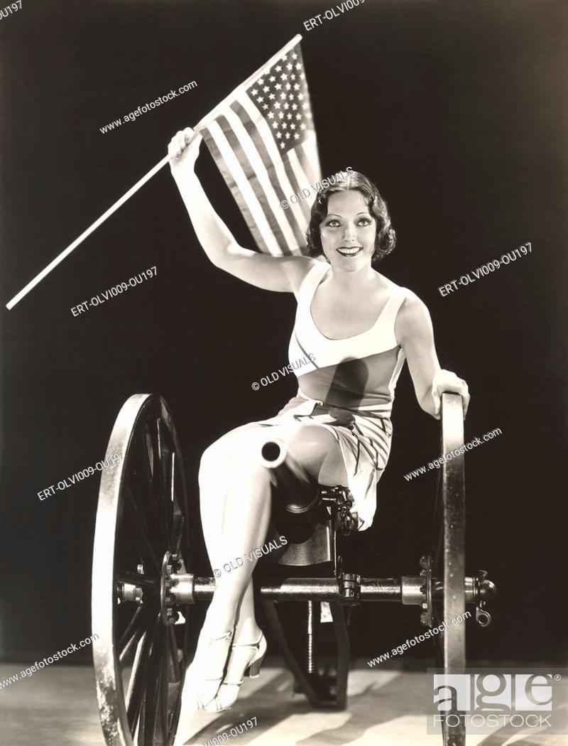 Photo de stock: Woman on cannon holding American flag.