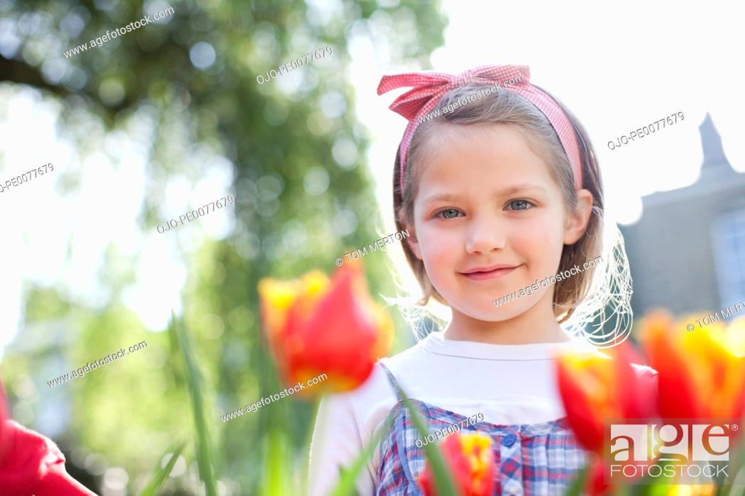 Stock Photo: Girl standing in field of flowers.