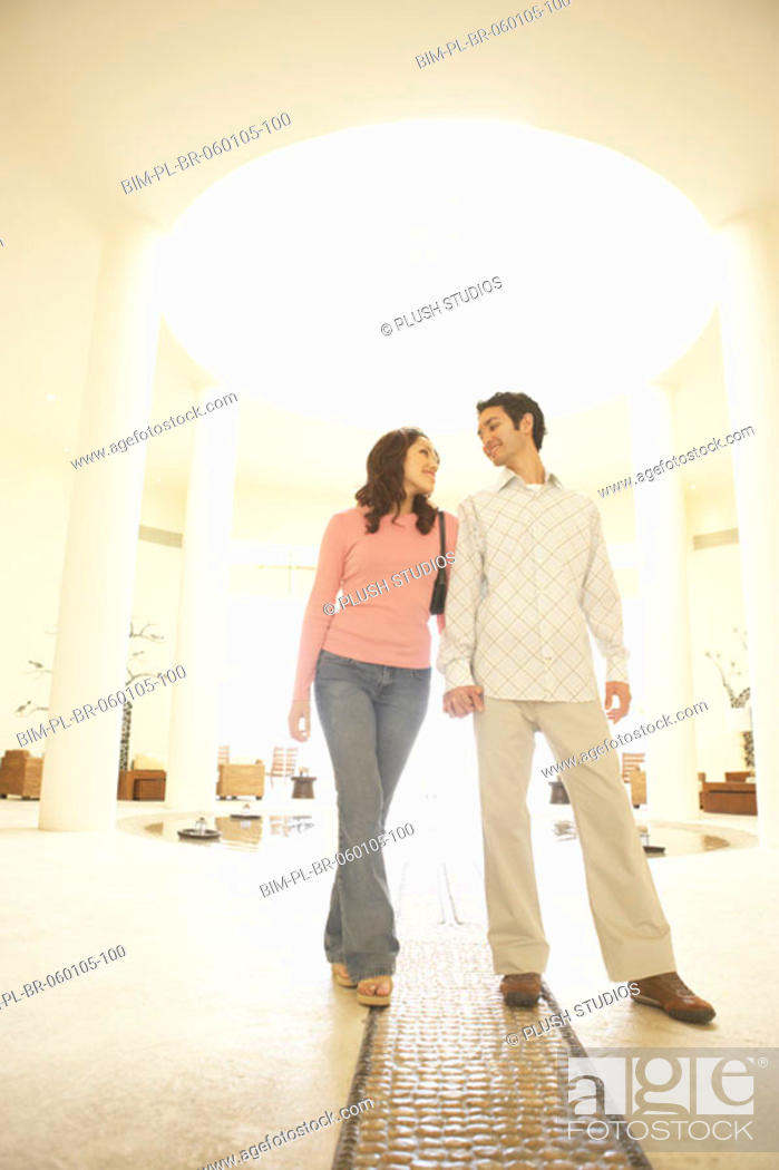 Stock Photo: Couple walking in hotel lobby, Los Cabos, Mexico.