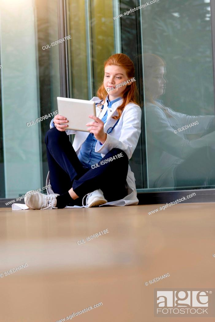 Stock Photo: Young female doctor looking at digital tablet at hospital entrance.