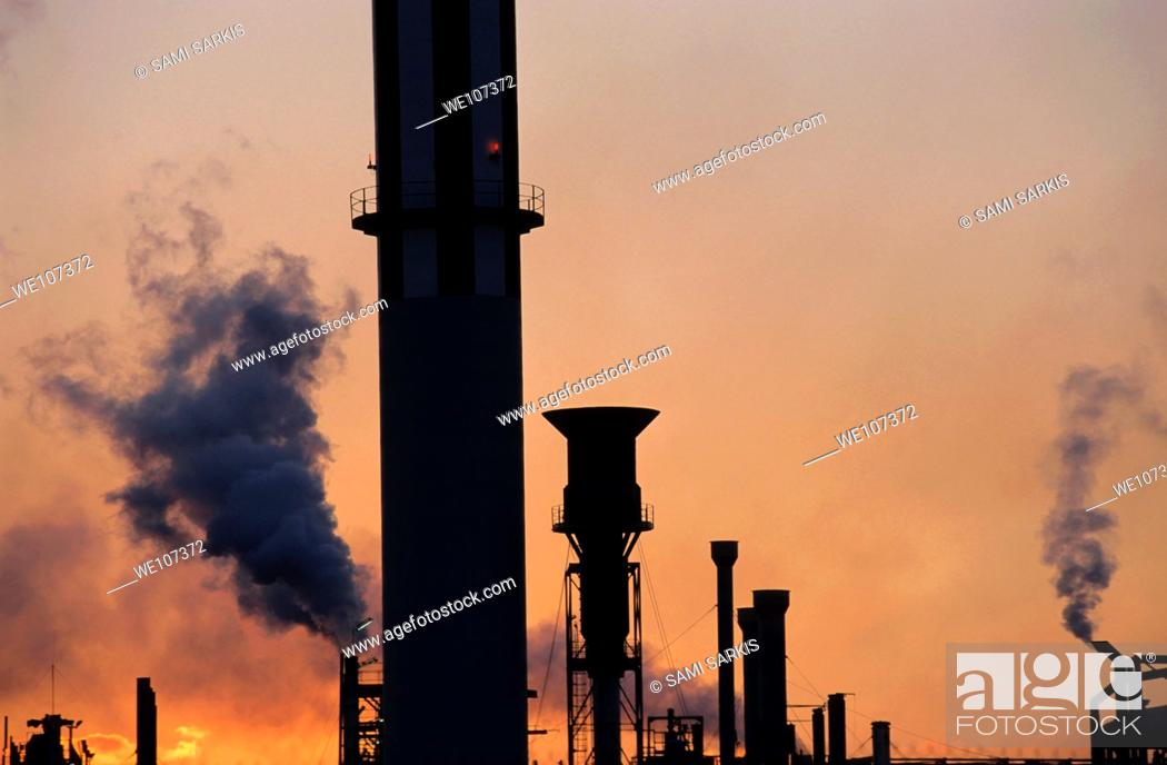 Stock Photo: Smoking chimneys of a petroleum refinery at sunset, Berre, France.