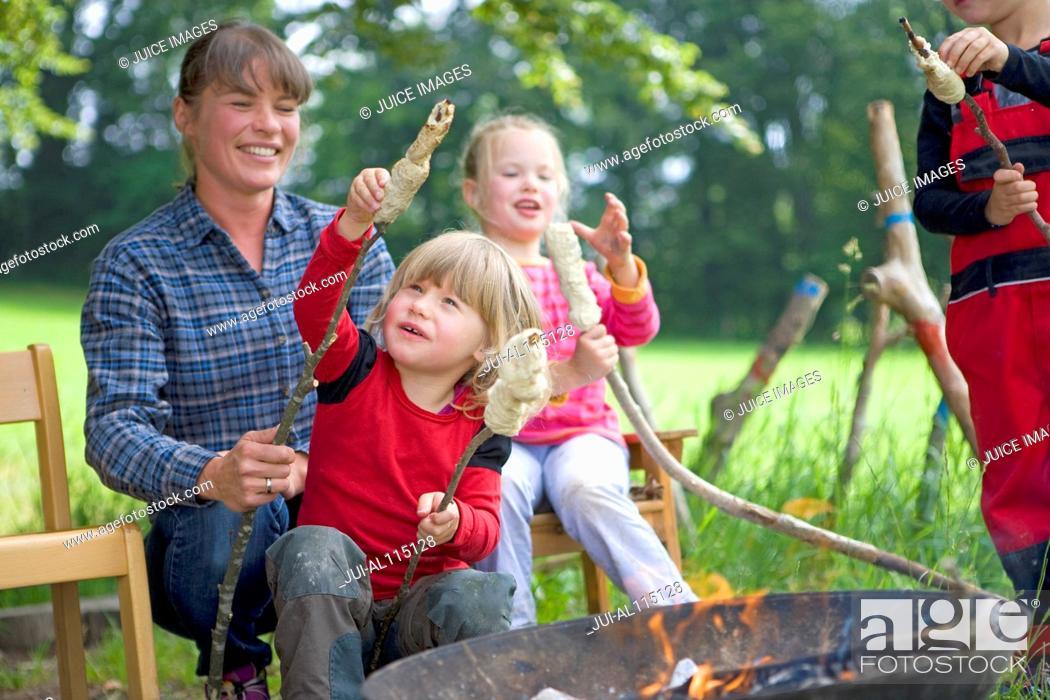 Imagen: Kindergarten kids preparing campfire bread in a wood kindergarten.