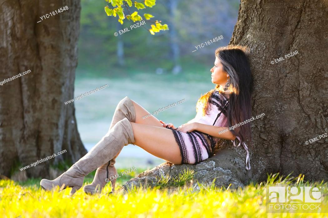 Stock Photo: Attractive young woman in the park daydreaming.