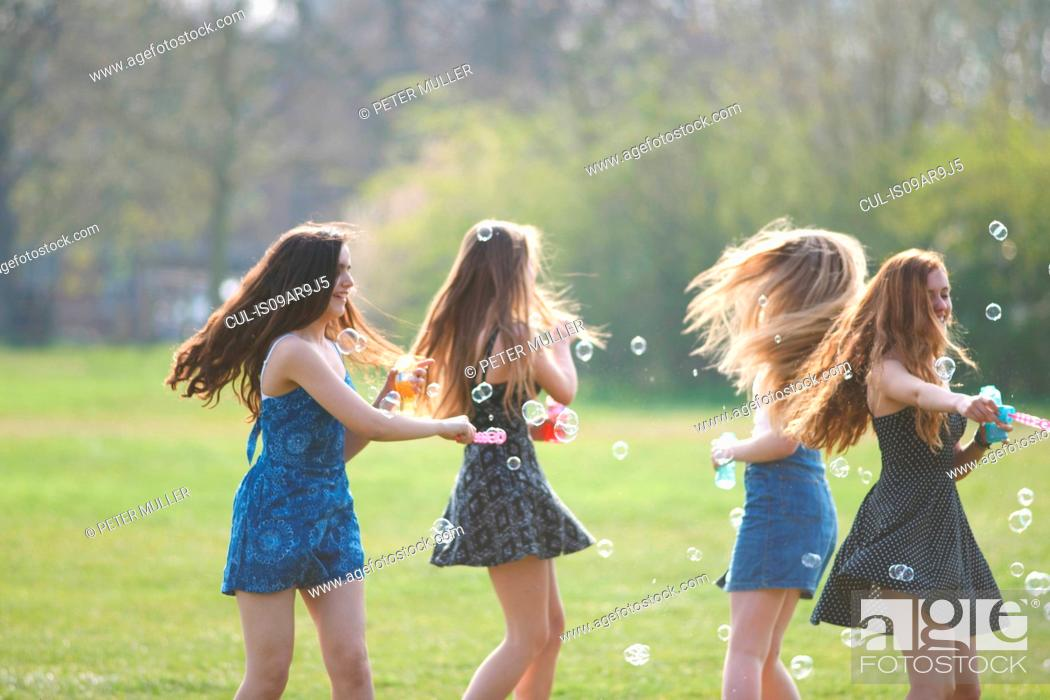 Stock Photo: Four teenage girls spinning bubbles with bubble wand in park.