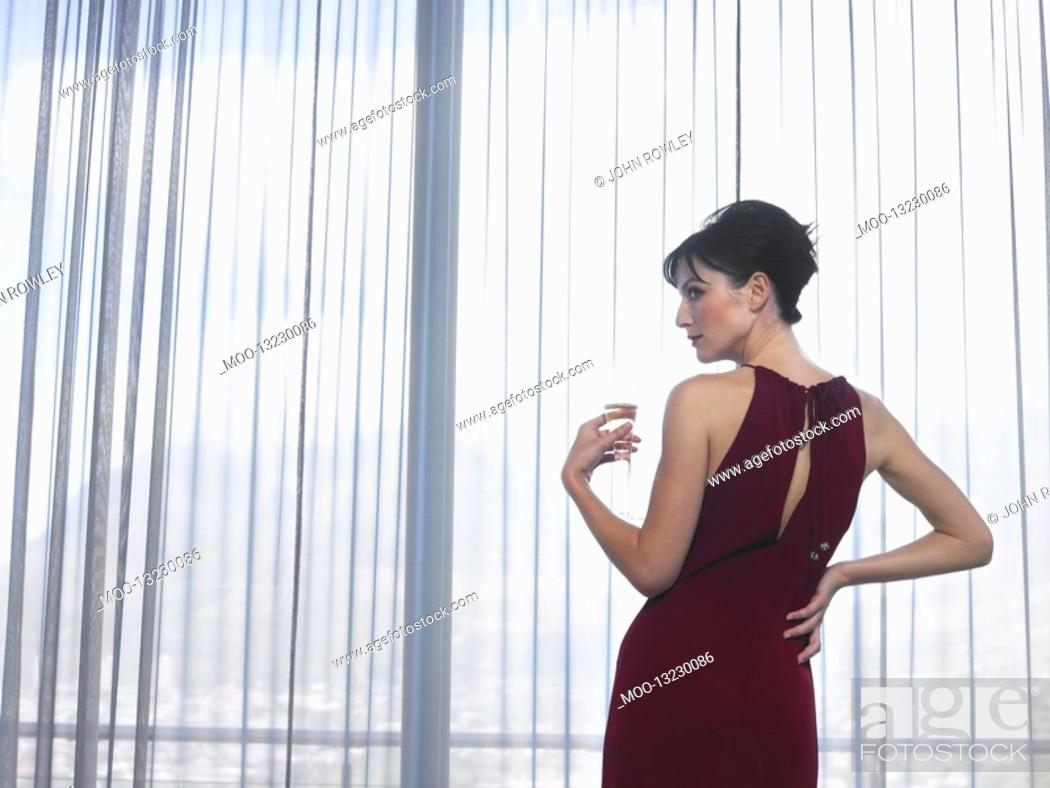 Stock Photo: Woman wearing elegant dress looking out of window indoors.