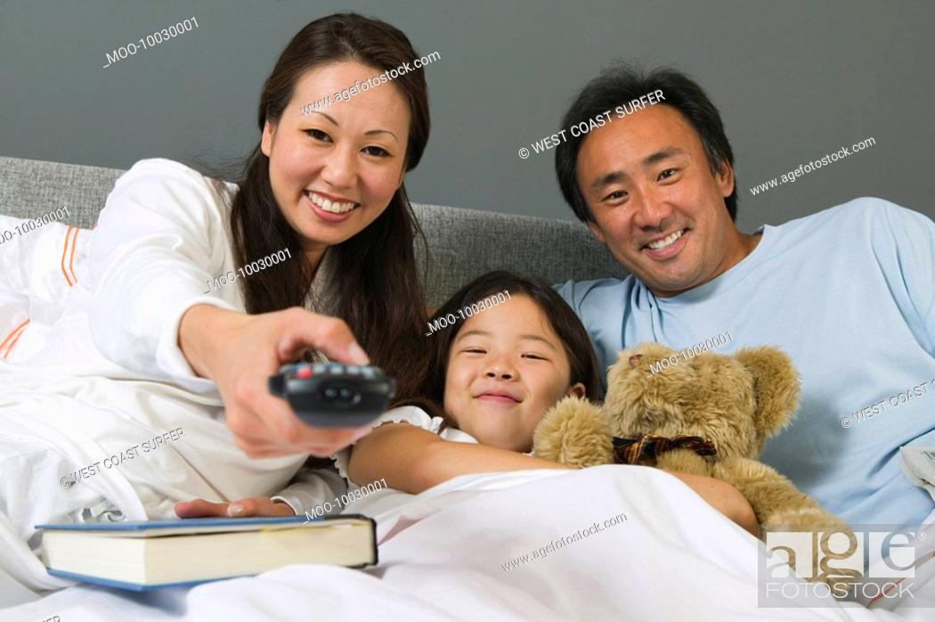 Stock Photo: Family Watching TV Together in Bed mother using remote control.