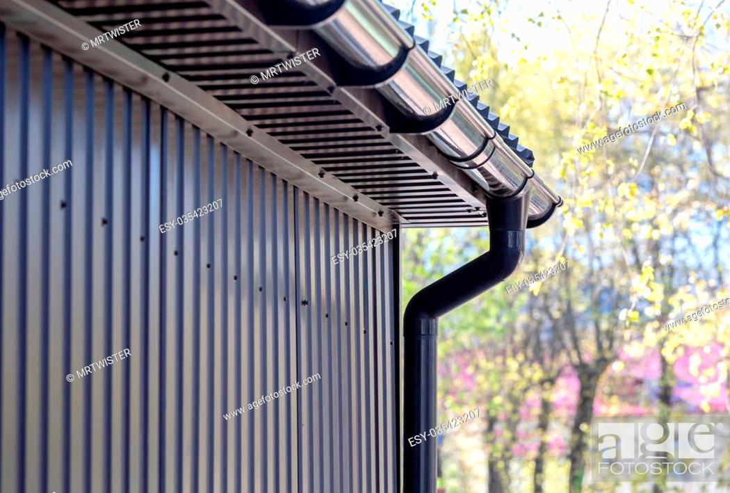 Stock Photo: brown siding wall with plastic rain gutter and drainpipe.