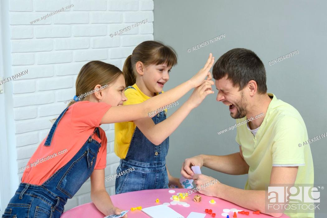 Stock Photo: Children beat dad scribble for losing the game.