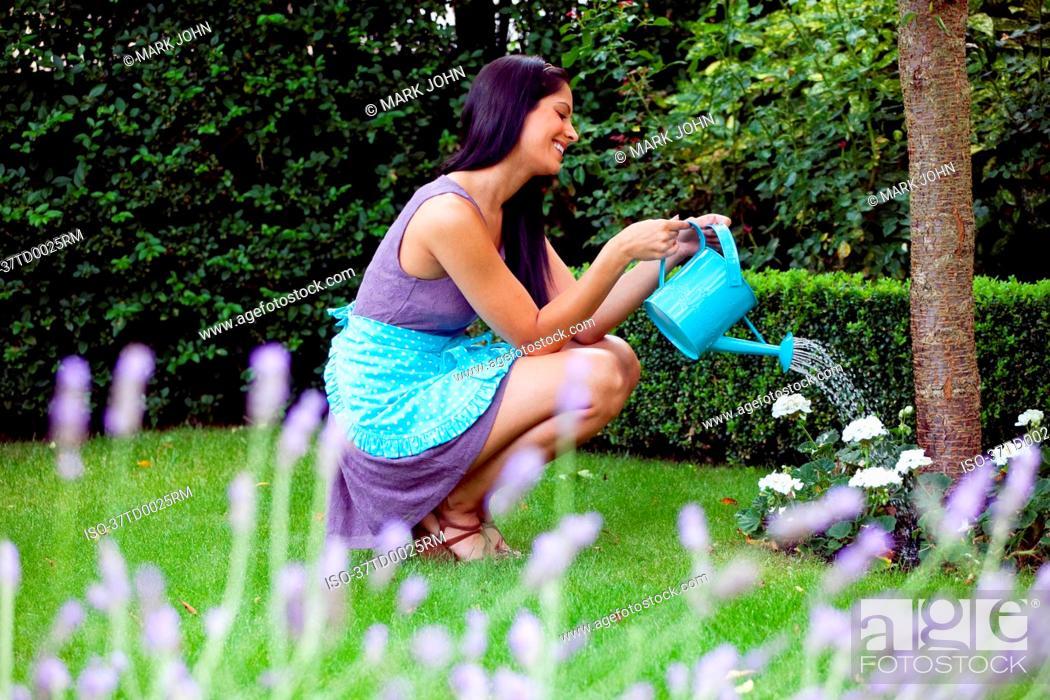 Stock Photo: Woman watering plants in backyard.