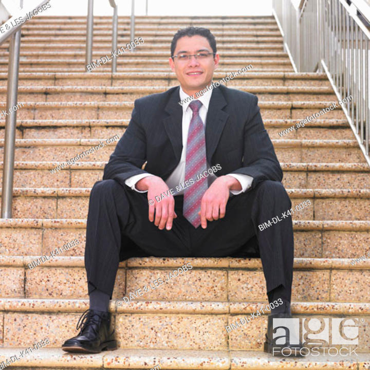 Stock Photo: Businessman smiling for the camera on a staircase.
