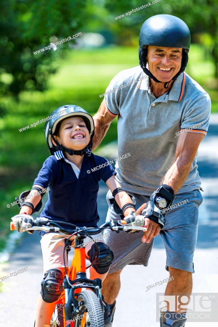 Stock Photo: Grandfather and grandson enjoying biking and roller skating.