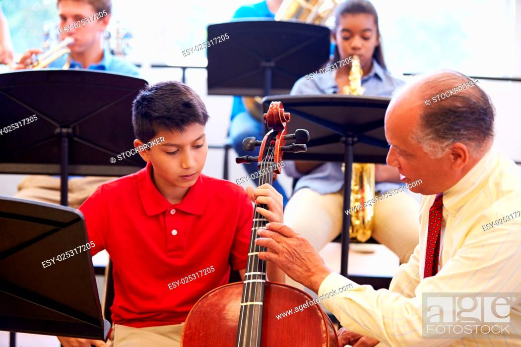 Imagen: Boy Learning To Play Cello In High School Orchestra.